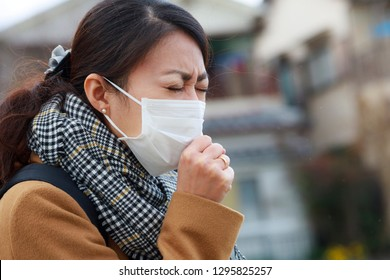 Woman wearing medical mask and coffing
