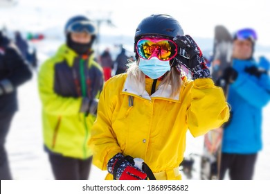 Woman wearing a medical mask during COVID-19 coronavirus on a sunny winter day at a ski resort