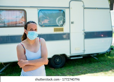 Woman wearing medical mask standing in front of camping trailer in a resort.