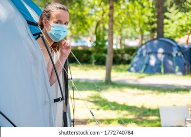 Woman wearing medical mask stepping out of camping tent.