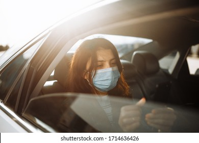 Woman wearing a medical sterile mask in taxi car on a backseat looking out of window checking her cell phone. Girl passenger waiting in a traffic jam during coronavirus quarantine. Healthcare concept