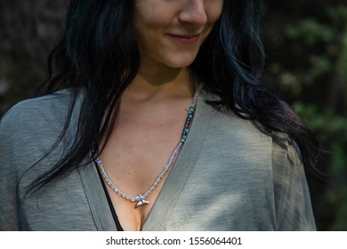 Woman wearing mineral stone mala necklace with wale tale silver pendant