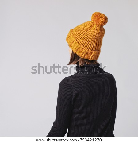 f157abba6bc Woman wearing mustard knit beanie hat with big pom pom and black turtleneck isolated  on grey