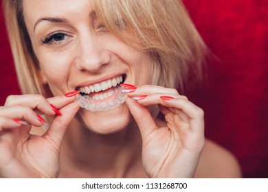 Woman wearing orthodontic silicone trainer. Invisible braces aligner, appliance for dental correction