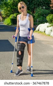 Woman wearing an orthopedic leg brace with adjustable straps to immobilise her leg following surgery or an accident walking on crutches outdoors
