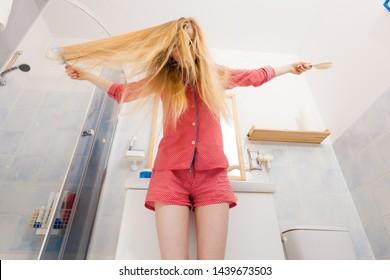 Woman wearing pajamas in bathroom having fun while brushing her long blonde hair, windblown hairdo, shot from bottom.