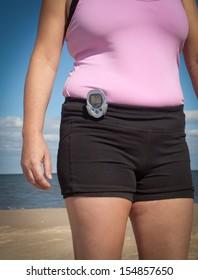 Woman wearing a pedometer walking on the beach