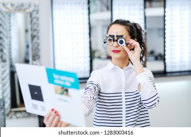 Woman wearing phoropter and holding brochure. Optician's shop interior.