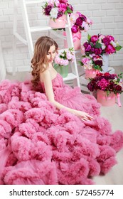Woman wearing pink colored fluffy dress near ladder with flowers. Vertical studio shot.
