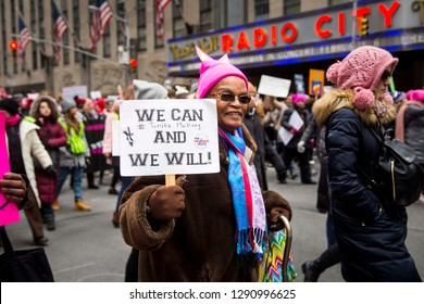 "Woman wearing a pink hat holds a sign ""We can and we will! - The Women's Vote"" while walking in the streets of NYC during the Women's March - New York, NY, USA January 1/19/2019 Women's March"