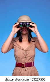 A woman wearing a pith helmet searching with a pair of binoculars, blue background with copy space.