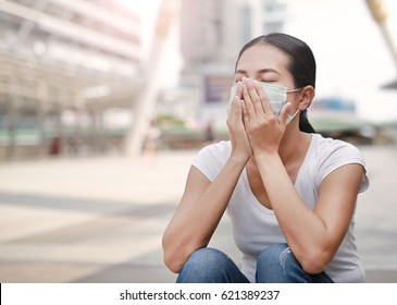 Woman wearing protective mask to protect pollution and the flu sitting at public area.