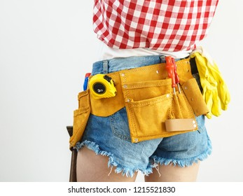 Woman wearing protective workwear toolbelt on jeans shorts. Girl working at flat remodeling. Building, repair and renovation.