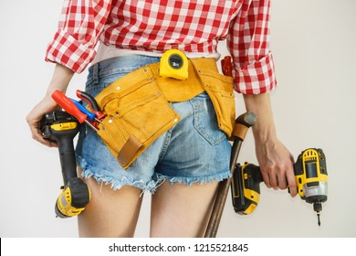 Woman wearing protective workwear toolbelt using drill. Girl working at flat remodeling. Building, repair and renovation.