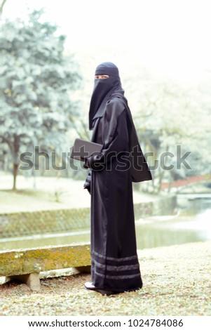 woman wearing purdah reading book on stock photo edit now