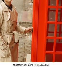 Woman wearing rain coat near telephone box