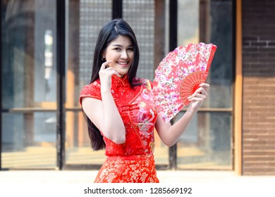 Woman wearing red cheongsam dress and holding China blow. The Year of the Pig, Chinese New Year concept.
