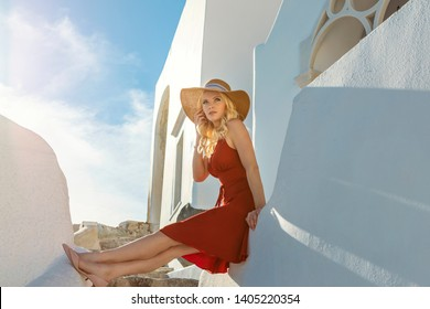 bl​ond woman wearing a red dress, on a staircase, in Oia on Santorini