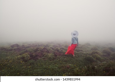 Woman wearing red dress and white hat walking in fog mountains