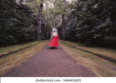 Woman wearing red dress and white hat walking in tropical jungle forest