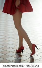 Woman wearing red elegant skirt and red high heel shoes. Sexy legs in footwear.