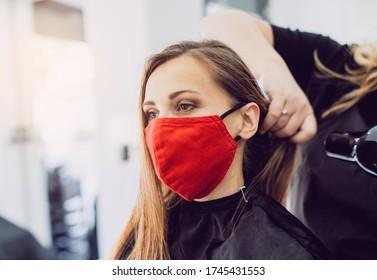 Frauen mit roter Gesichtsmaske erhalten frische Stilelemente in einem Friseursalon