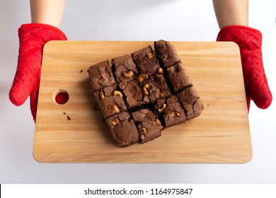 Woman wearing red gloves protect her hands holding chocolate brownie on wood chopping board on white table background