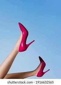 Woman wearing red high heel shoes in the blue sky.