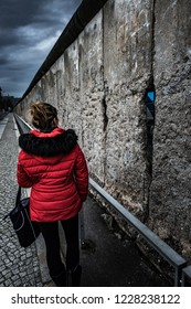 Woman wearing red jacket visits remains of Berlin Wall Germany