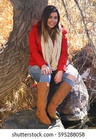Woman wearing red jacket in winter sitting near creek