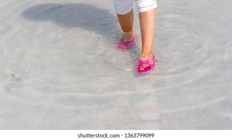Woman wearing red or pink slipper walking on the famous tourist destination Salt Lake (Turkish: Tuz Golu) is the second largest lake in Turkey.