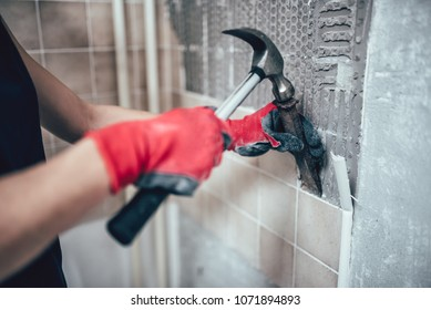 Woman wearing red safety gloves removing wall tails in the kitchen