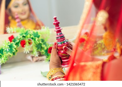 A woman wearing red sari and bangles holding a wooden carved traditional box of vermilion or sindoor