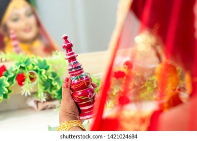 A woman wearing red sari holding a wooden carved traditional box of Vermilion or sindoor in a wedding ceremony