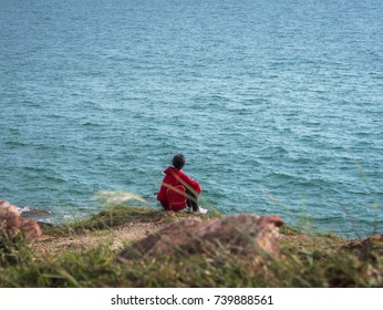 A woman wearing a red shirt sat watching the sea alone, she looked lonely.