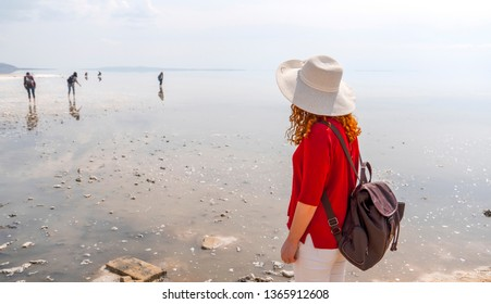 Woman wearing red shirt and white hat watching Salt Lake (Turkish: Tuz Golu) is the second largest lake in Turkey.
