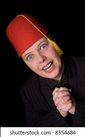 Woman wearing a red shriners fez over a black background