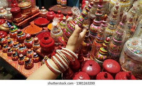 A woman wearing red and white glass bangles checking a wooden carved traditional box to hold vermillion or sindoor in a shop in varanasi.