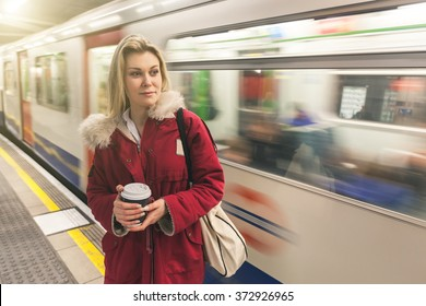A woman wearing a red winter coat is waiting for the train on the platform. She is on the underground and is holding a cup of coffee. On the background there is a blurred train.