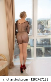 Woman wearing a revealing black fishnet body stocking looking out of a window.