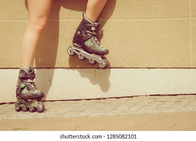 Woman wearing roller skates in town. Female being sporty during summer time.