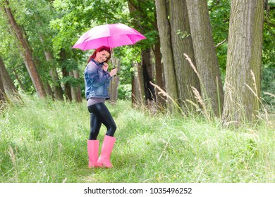 woman wearing rubber boots with umbrella in spring nature