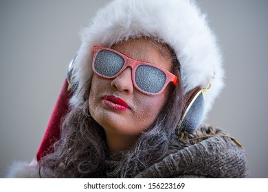 Woman wearing Santa Claus hat and sunglasses listening to music with her headphones. Winter season series fashion portrait
