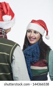 Woman wearing a Santa hat and smiling at her boyfriend