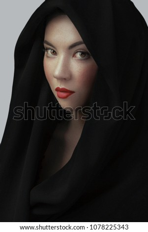 39bbe7fc210 Woman wearing scarf with hood. Beautiful woman big eyes covers her face  with a black cloth. Red lips girl under hood. isolated on gray background -  Image
