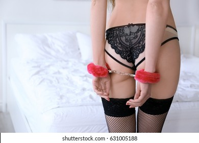 Woman wearing sexy fluffy handcuffs on her wrists in bedroom