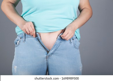 The woman is wearing small pants on grey background