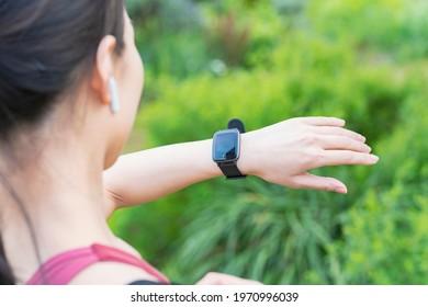 A woman wearing sportswear and operating a smartwatch