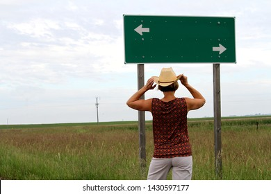 A woman wearing a straw cowboy hat looking at a sign showing two arrows.  She is at a fork in the road and has to decide which direction she will go.  A grass prairie is seen in the background.