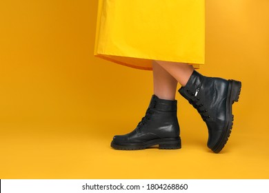Woman wearing stylish boots on yellow background, closeup. Space for text